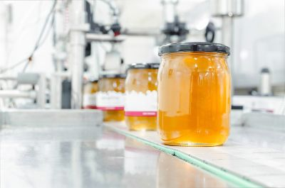 Food and beverage industry: Glass of jam or honey on manufacturing belt about to be processed in a labelling machine