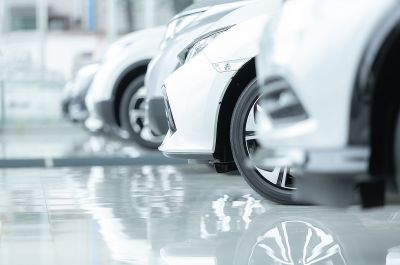 Automotive industry: white cars lined behind each other with their shadows reflecting on the floor