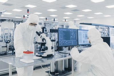Pharma and MedTech industry: two employees in white protecting suits working in a laboratory on computer and on a microscope in a biological or pharmaceutical setting