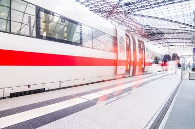 Railway industry: train arriving in light-flooded train station with motion blur